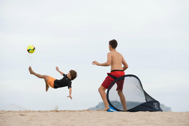 niños jugando a fútbol en la playa
